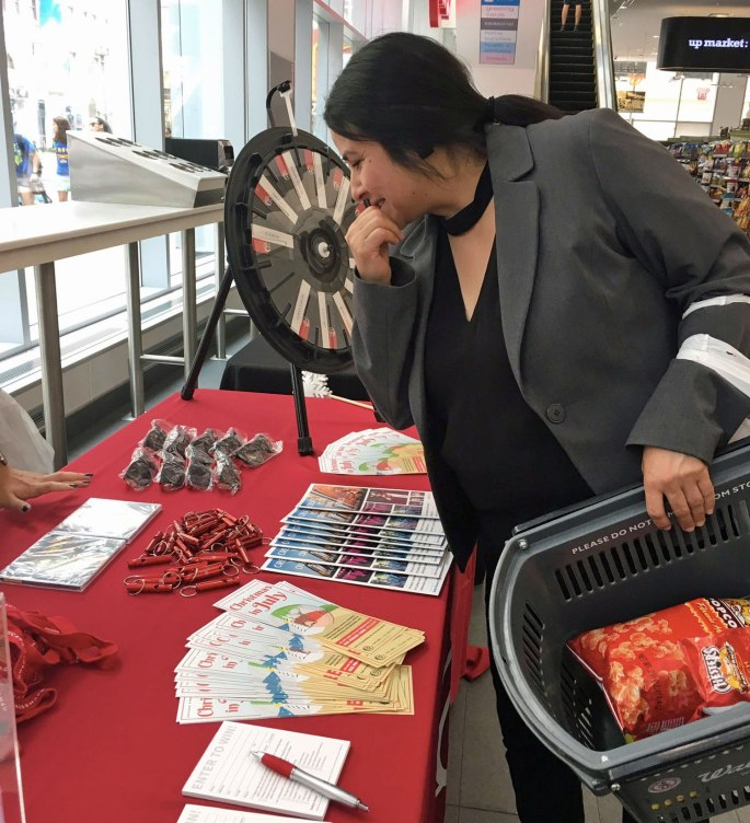shopper checks out the prize wheel and swag